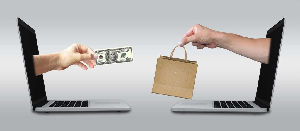ecommerce - two laptops - two hands - a paper bag and 100 dollar bill - exchange
